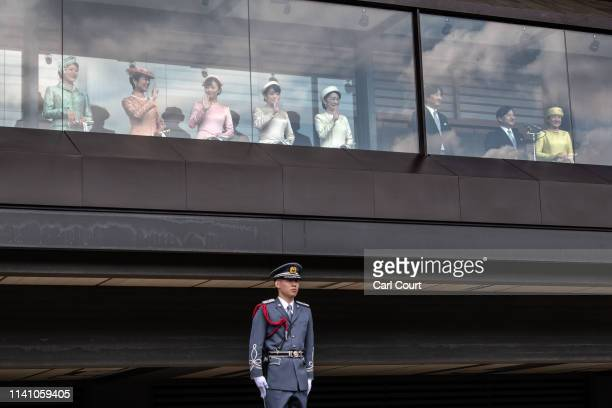 An Imperial Guardsman stands watch as members of the Japanese royal family wave to the public from the balcony of the Imperial Palace after a speech...