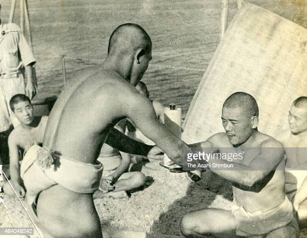 An Imperial Japanese Navy soldier receives a bottle of beer as he won five consecutive sumo matches held on the battleship Kashima circa May 1942 in...