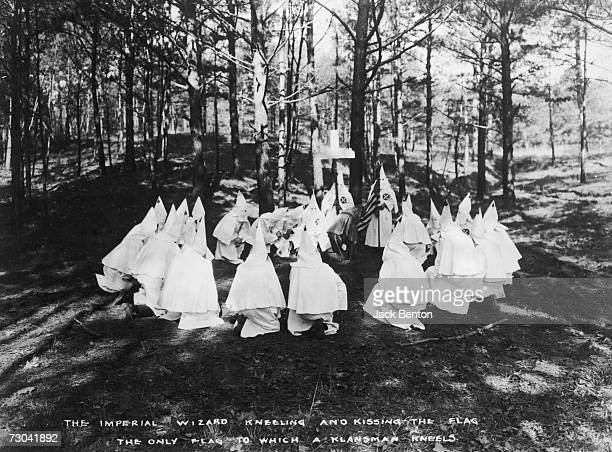 An Imperial Wizard of American white supremacist organization the Ku Klux Klan kneels to kiss the Stars and Stripes during a Klan ceremony in...