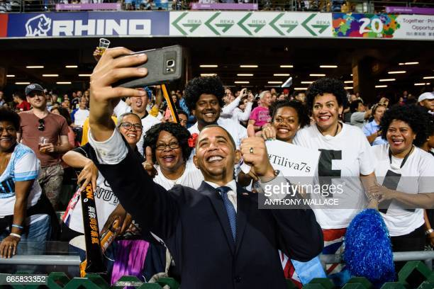 An impersonator of former president of the US Barack Obama poses for a selfie with Fiji rugby fans as he makes an appearance on the first day of the...