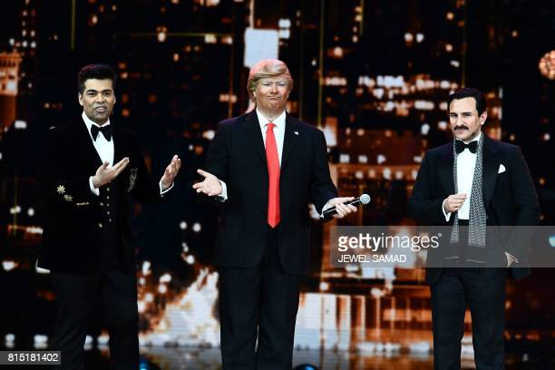 An impersonator of US President Donald Trump performs on stage as Bollywood actor Saif Ali Khan and director/producer Karan Johar look on durig IIFA...