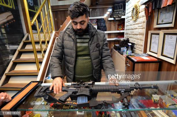 An imployee of a gun shop shows a rifle in the northern Iraqi city of Mosul on January 28 2019 Hunting rifles pistols and towers of ammunition...