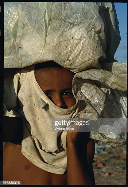 An impoverished Brazilian boy who lives off garbage pickings from the dump covers his face with a shirt