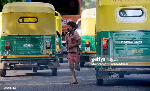 An impoverished handicapped Indian child begs for money from vehicles on a street in New Delhi on October 2 2010 The Indian capital is scheduled to...