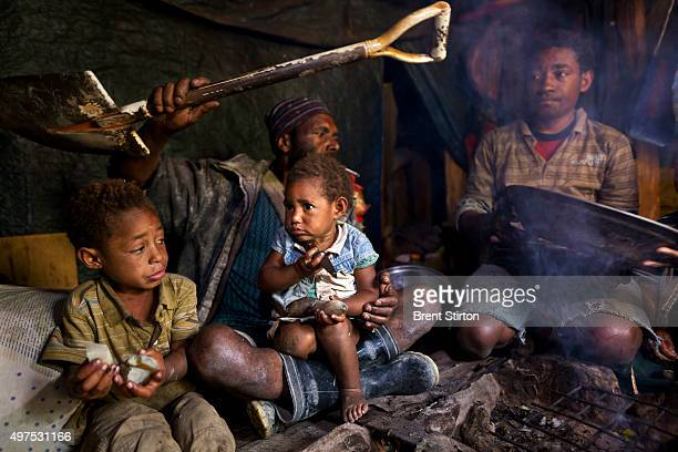 An impoverished Papuan family cooks breakfast before going out to illegally prospect in a mine tailings river with heavy metal laden waters on the...