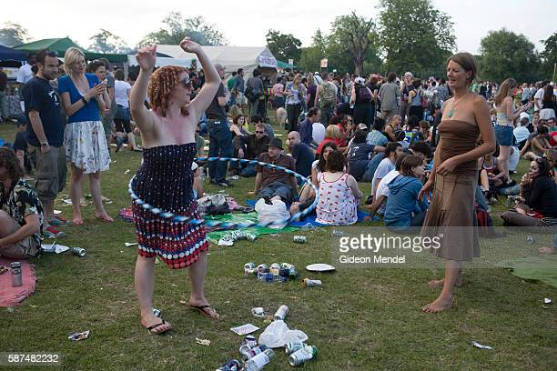 An impromptu Hula hoop lesson takes place as people sit and and socialise at the end of a long day of music and entertainment at Stokefest This is a...