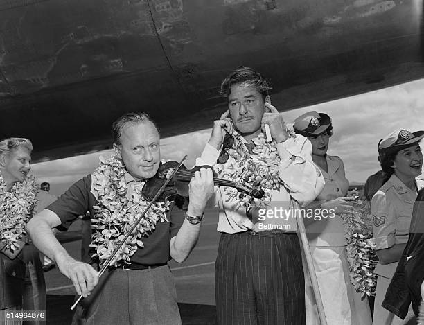 An impromptu show at the Honolulu Airport brought howls of laughter from spectators when radio comedian Jack Benny and movie actor Errol Flynn...