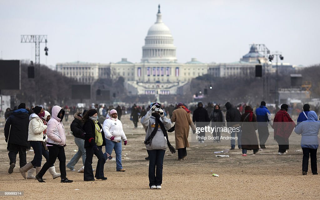 An inaugural spectator stops to take one last picture as the crowd of an estimated 2 million people filters off the mall.
