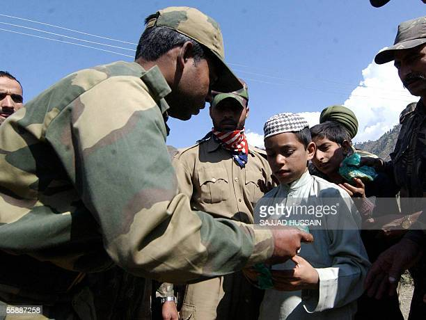 An Indain army solider distributes relief material to affected civilians at Tangdar some 150 kms north of Srinagar 10 October 2005 The 08 October...