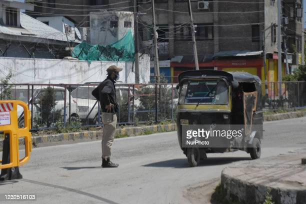 An Indain policeman stops a auto rickshaw on a deserted street during Covid-19 curfew in Srinagar, indian Administered Kashmir on 25 April 2021....