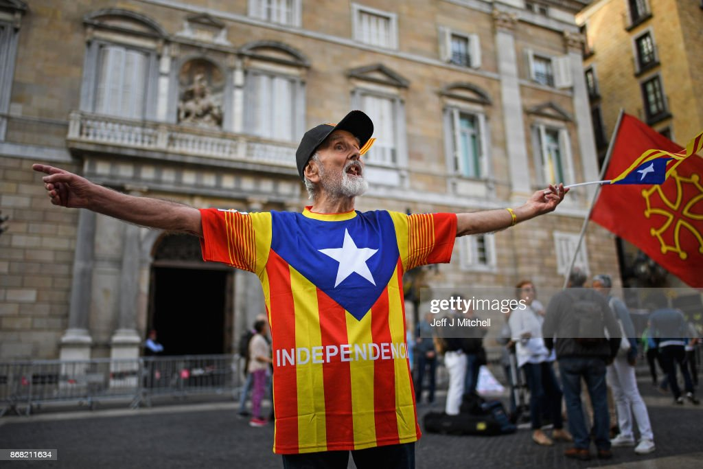 An independence supporter waves a flag outside the Palau Catalan Regional Government Building as Catalonia returns to work following last week's decision by the Catalan parliament to vote to split from Spain, on October 30, 2017 in Barcelona, Spain. The Spanish government has responded by imposing direct rule and dissolving the Catalan parliament.