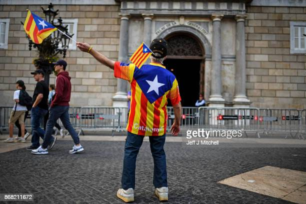 An independence supporter waves a flag outside the Palau Catalan Regional Government Building as Catalonia returns to work following last week's...