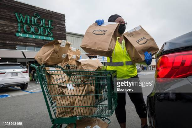 An independent contractor wearing a protective mask and gloves loads Amazon Prime grocery bags into a car outside a Whole Foods Market in Berkeley,...