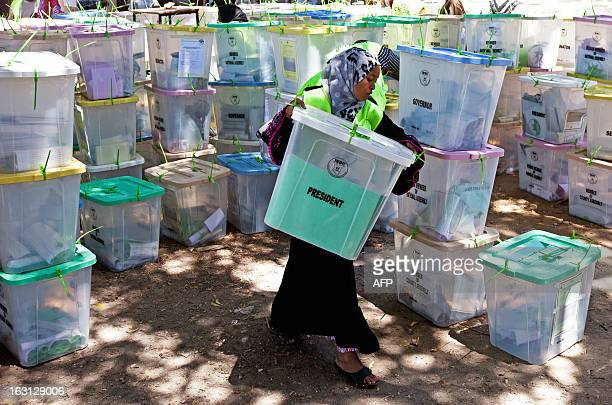 An Independent Electoral and Boundaries Commission official carries closed ballot boxes to be counted in Mombasa on March 5 2013 Kenyans nervously...