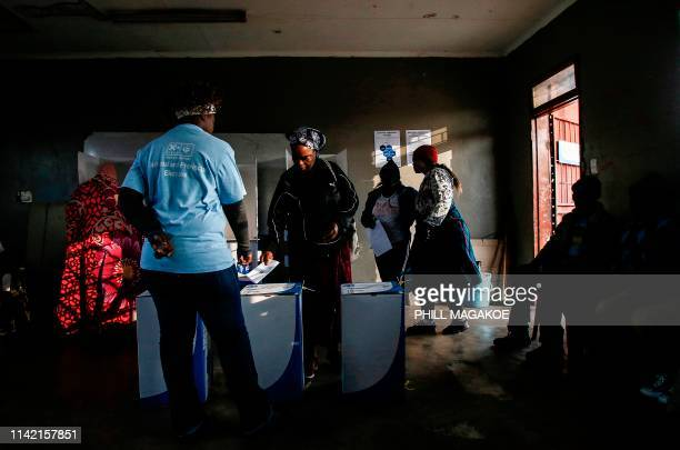 An Independent Electoral Commission official assists a woman to cast her vote at Rakgatla secondary school polling station during South Africa's...