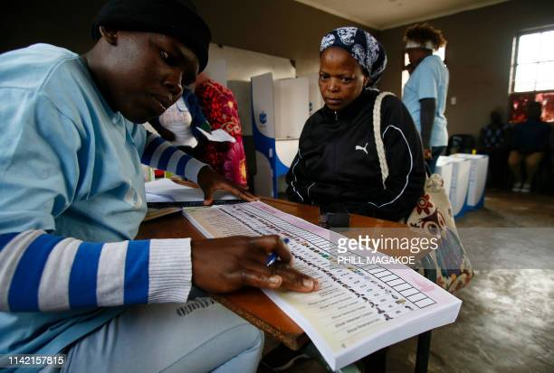 An Independent Electoral Commission official selects a ballot paper to give to a woman moments before she casts her vote at Rakgatla Secondary School...