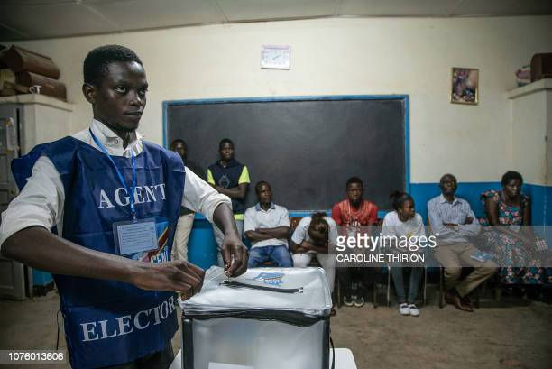 An Independent National Electoral Commission agent seals a ballot box in front of observers at the Kitendo voting centre in Lubumbashi's Mapala...