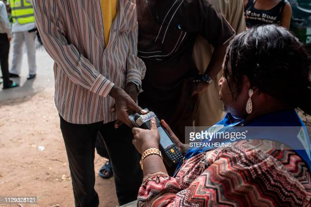 An independent National Electoral Commission official uses a biometrics meter to take the finger print of a registered voter at a polling unit in...