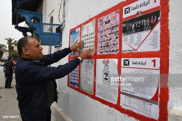 An independent Tunisian candidate hangs campaign posters for the upcoming municipal elections in the Tunis suburb of Ariana on April 14 2018 Tunisia...