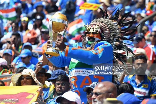 An India fan holds up a replica world cup trophy in the crowd during the 2019 Cricket World Cup group stage match between Sri Lanka and India at...