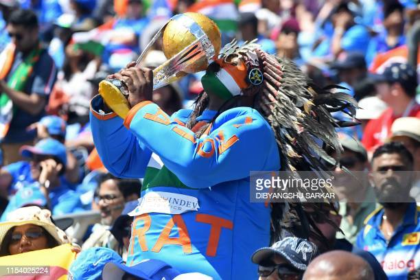 An India fan holds up and kisses a replica world cup trophy in the crowd during the 2019 Cricket World Cup group stage match between Sri Lanka and...