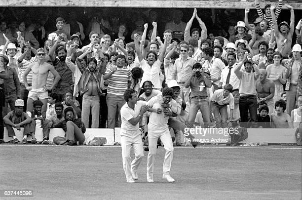 An India fan leaps onto the back of captain Kapil Dev in celebration after the skipper dismissed his opposite number West Indies' Viv Richards with a...