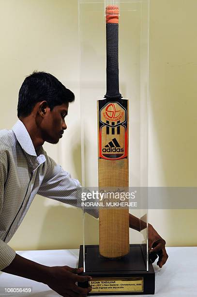 An India Fine Art gallery staff cleans a display case bearing Indian cricketer Sachin Tendulkar's autographed bat to be placed under auction in...