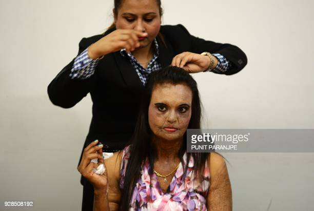 TOPSHOT An Indian acid attack survivor gets her hair done before a fashion show as part of a campaign to spread the message 'Stop Acid Sale' in Thane...