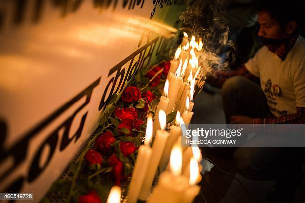 An Indian activist lights a candle during a vigil to mark the second anniversary of the fatal gangrape of a student in the Indian capital at the bus...