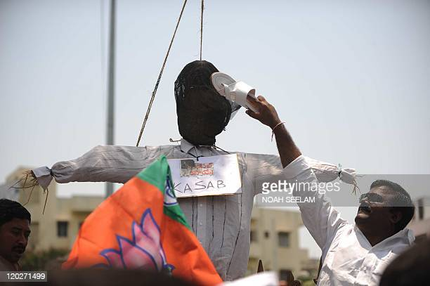 An Indian activist of the main opposition Bharatiya Janata Party uses a shoe to hit an effigy representing Pakistani Mohammed Ajmal Kasab in...