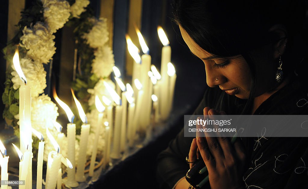 An Indian activist prays as she takes part in a candlelight vigil in Kolkata on December 30, 2012, after the cremation ceremony for a gangrape victim. The victim of a gang-rape and murder which triggered an outpouring of grief and anger across India was cremated at a private ceremony, hours after her body was flown home from Singapore. A student of 23-year-old, the focus of nationwide protests since she was brutally attacked on a bus in New Delhi two weeks ago, was cremated away from the public glare at the request of her traumatised parents. AFP PHOTO/Dibyangshu SARKAR