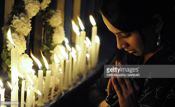 An Indian activist prays as she takes part in a candlelight vigil in Kolkata on December 30 after the cremation ceremony for a gangrape victim The...