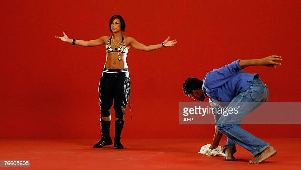 An Indian actress gestures as a support staff member cleans the floor and background inbetween the filming of a musical number on a set at Kamlistan...