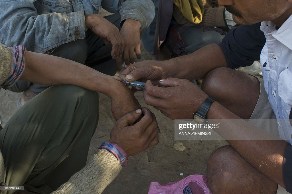 An Indian addict injects drugs into the fore-arm of a fellow user in the old sector of New Delhi on December 1, 2012. Drug use in India is on the rise but there are no proper statistics on the number of people suffering from this 'hidden disease' with the first and last national survey on drug abuse carried out in 2000-01 and showed a figure of 70 million drug users in the country. AFP PHOTO/ Anna ZIEMINSKI