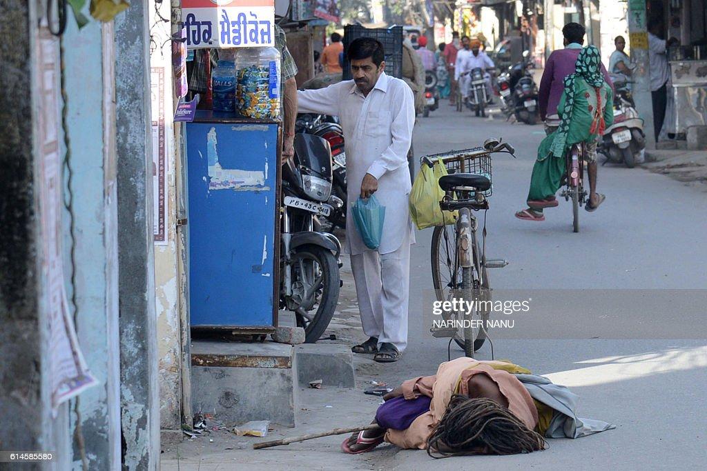 An Indian Aghori Sadhu sleeps on the road outside a medicine shop in Amritsar on October 14 2016 / AFP / NARINDER NANU