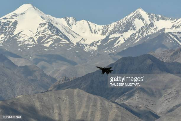 An Indian Air Force aircraft is seen against the backdrop of mountains surrounding Leh, the joint capital of the union territory of Ladakh, on June...