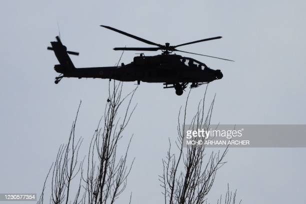An Indian Air Force Apache helicopter flies over Leh, the joint capital of the union territory of Ladakh bordering China, on January 14, 2021.