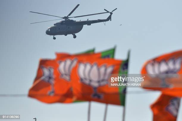 An Indian Air Force helicopter carrying Indian Prime Minister Narendra Modi is seen over Bharatiya Janata Party flags before a gathering...