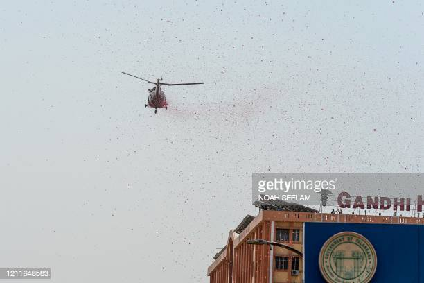 An Indian Air Force helicopter drops rose petals from the sky to pay tribute to all the staff of the Gandhi Hospital and police personnel involved in...