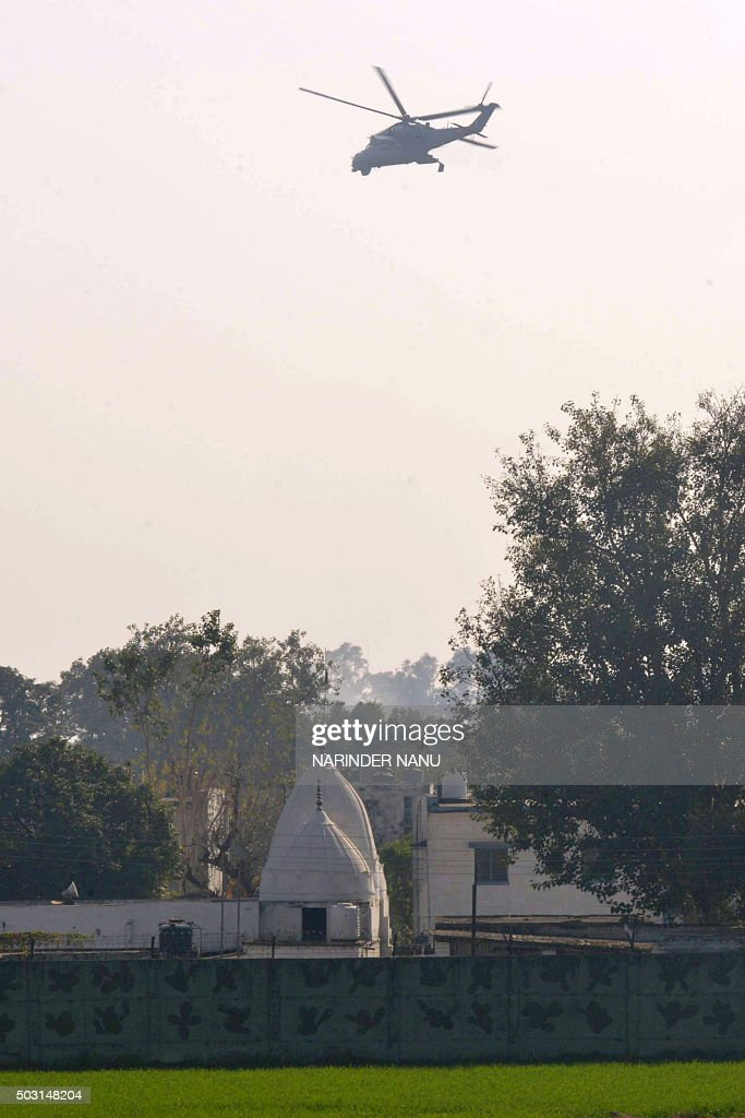 An Indian Air Force helicopter flies over an airforce base in Pathankot on January 2 during an ongoing attack on the base in the northern Indian...