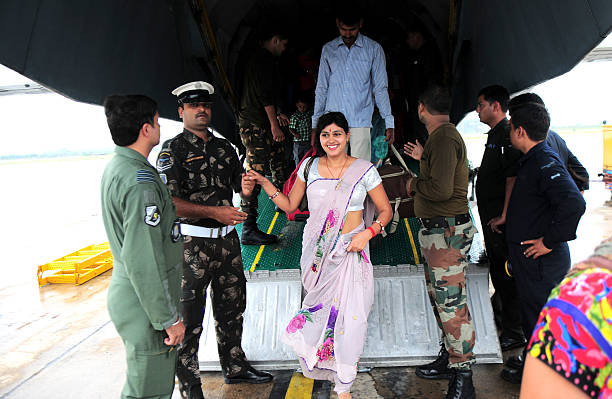 An Indian Air Force officer assists a lady to get down as flood victims arrive at the air force station after being rescued by the Indian armed...