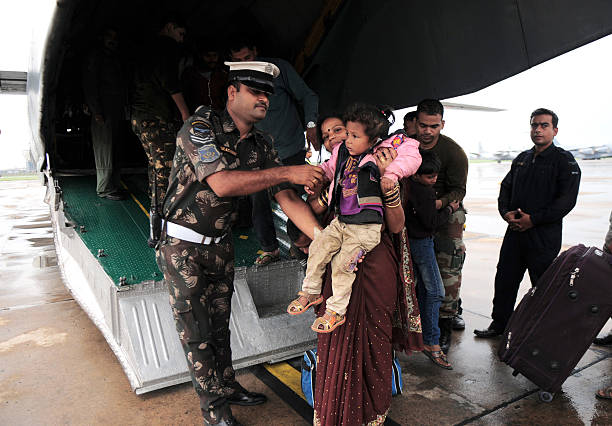 An Indian Air Force officer assists a lady with child to get down as flood victims arrive at the air force station after being rescued by the Indian..
