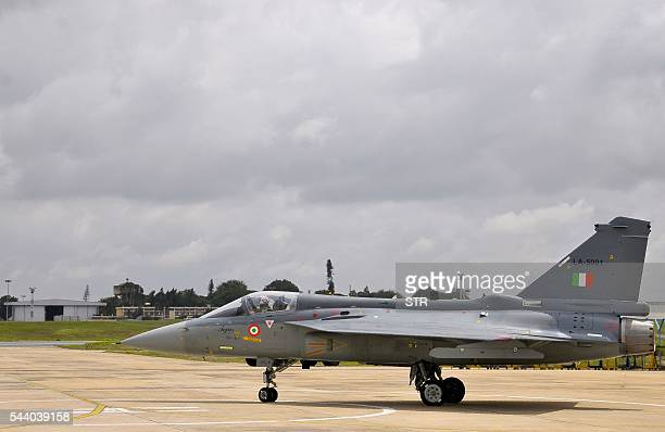 An Indian Air Force pilot taxies a newly commissioned Tejas or Light Combat Aircraft on a runway in Bangalore on July 1 during a ceremony in the...