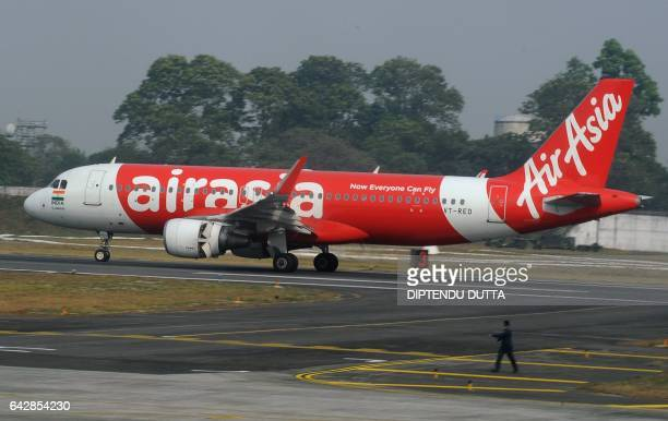 An Indian airport staff member walks next to an AirAsia airplane after it landed on its inaugural flight from New Delhi to Bagdogra Airport some 20km...