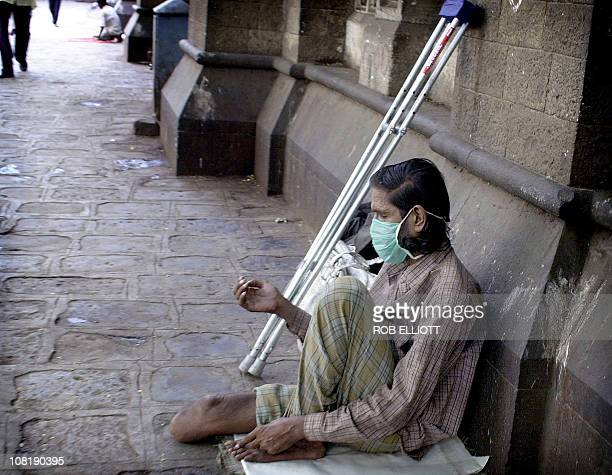 An Indian amputee wearing a mask sits on the sidewalk with his hand out waiting for donations from passing pedestrians in the streets of Bombay 10...