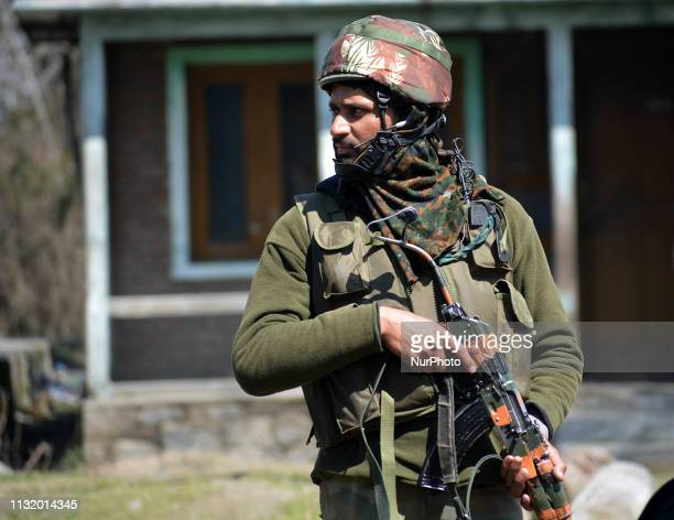 An Indian army man guards the main road near the gunbattle site in Hajin area of Bandipora some 35 kilometers from Srinagar Kashmir on March 22 2019...