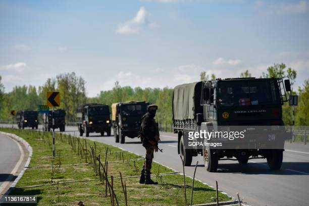 An Indian army man seen standing alert as the Indian army convoys moves on the National Highway on the outskirts of Srinagar The Indian authorities...