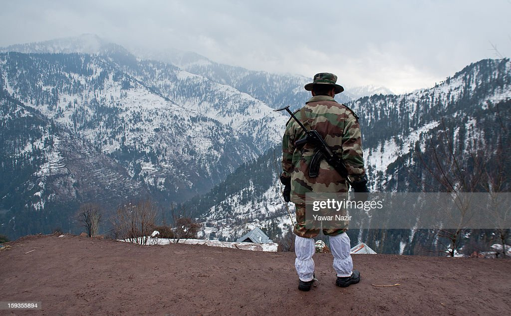 An Indian army officer looks towards Pakistan Administered Kashmir Churunda village on January 12, 2013, northwest of Srinagar, the summer capital of Indian Administered Kashshmir, India. The village with a population of a little over 12,000 people has been bearing the brunt of cross-fire between nuclear rivals India and Pakistan. Last week a Pakistan solider was killed across the Line of Control (LOC), a military line that divides Indian-administered Kashmir from the Pakistan-administered Kashmir at this village. People living along the LoC have continually been at risk due to hostility between the armies of the two rival nations. Last year, in November, three people, including a pregnant woman, had died after a shell fired from Pakistan landed on one of the houses in the village. Tension between Pakistan and India has escalated after a fresh skimirish along the border. Both countries have summoned each other's envoy to protest against unacceptable and unprovoked' attacks.