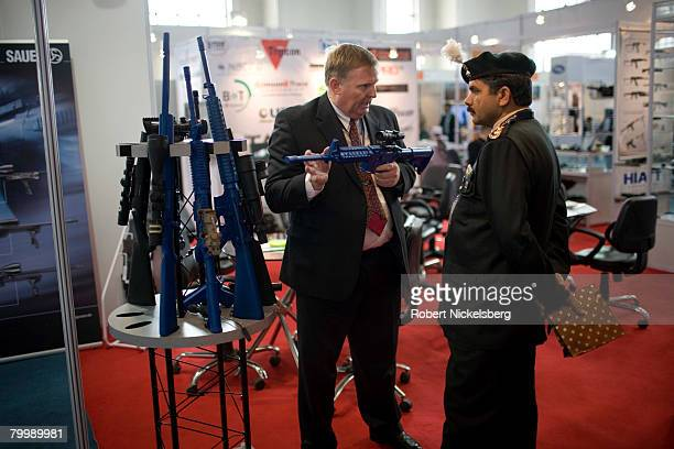 An Indian Army officer with the Ministry of Defense right listens to a western arms salesman explain rifle sighting devises February 18 2008 in New...