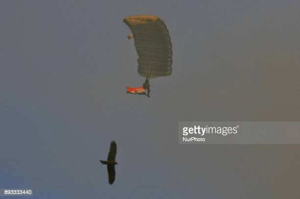 An Indian army paratrooper jumps from a plane carrying an Indian national flag during to mark the 46th anniversary of Vijay Diwas at RCTC ground on...